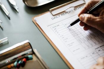 Eine Männerhand füllt eine medizinische Checkliste für einen Patienten aus