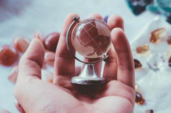 Eine offene Hand hält einen Globus aus Glas