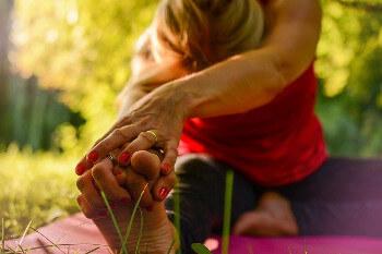 Eine Frau macht Yoga zur Rehabilitation auf einer Wiese