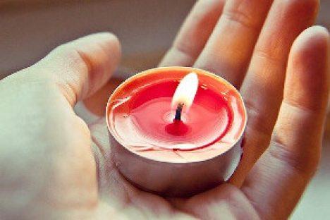 Hand hält brennende Kerze