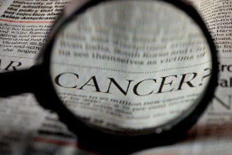 Lupe über Zeitung mit dem englischen Wort für Krebs