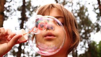 Ein Mädchen bläst Seifenblasen