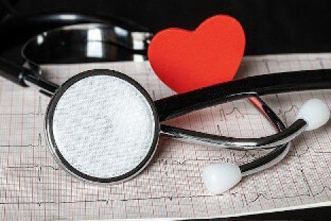 Ein Stethoskop, ein rotes Herz auf einem Ausdruck mit EKG Linien