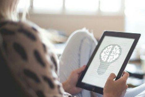Eine Frau hält ein Tablet Computer mit dem Modell eines Gehirn
