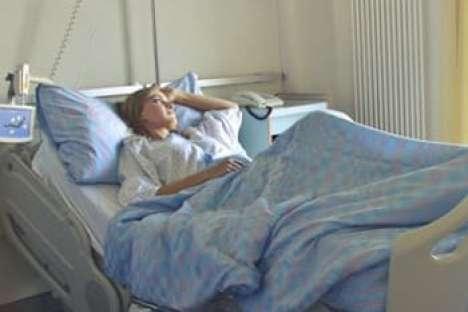 Eine Frau liegt in einem Krankenbett und sieht nachdenklich aus dem Fenster